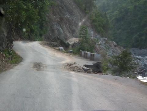 Dziura w drodze po podmyciu przez rzeke
